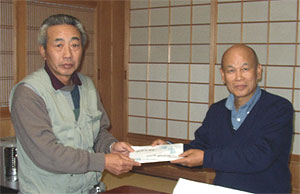 Kodama handed the donation to Mr. Isa